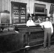 Jose De Jesus Rubi and son, Benito Rubi (behind bar). Winslow, Airzona. Circa 1920